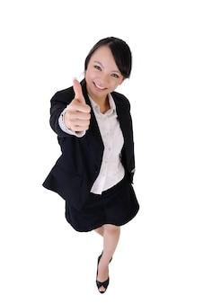 De gelukkige glimlachende bedrijfsvrouw geeft u een uitstekende zonde, volledig lengteportret dat op witte achtergrond wordt geïsoleerd.