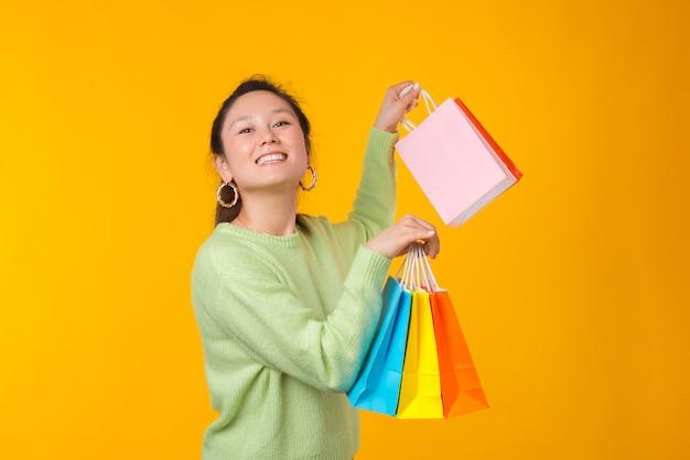 De gelukkige glimlachende dame houdt sommige kleurrijke document het winkelen zakken
