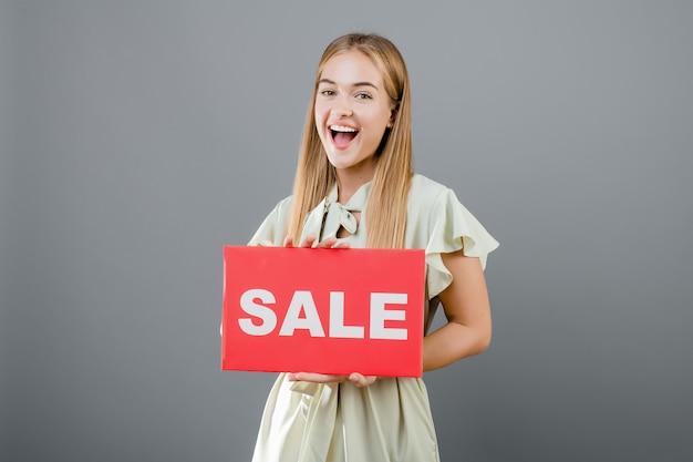 De gelukkige glimlachende die vrouw heeft verkoopteken over grijs wordt geïsoleerd