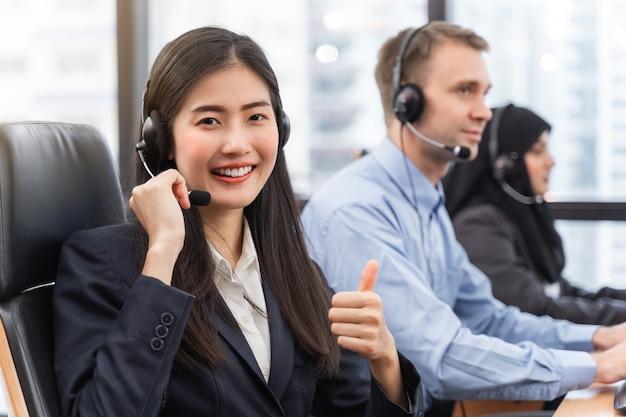 De gelukkige glimlachende exploitant aziatische vrouw is klantenserviceagent met hoofdtelefoons die aan computer in een call centre werken, die met klant spreken voor het helpen om het probleem op te lossen met duimen omhoog stellen