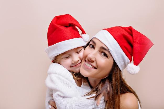 De gelukkige, glimlachende grappige moeder en dochter stellen en houden hun gezichten vast terwijl ze kerstmutsen dragen. een jonge mooie vrouw met heldere lippen houdt een meisje van 5 jaar vast.