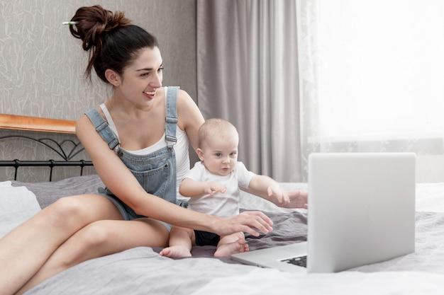 De gelukkige glimlachende jonge moeder met een klein kind werkt vanuit huis, zittend op het bed.