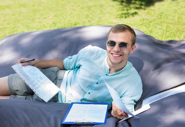 De gelukkige glimlachende jonge student bestudeert in openlucht, leggend op een groot kussen.