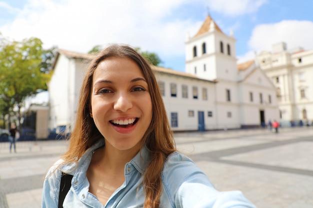 De gelukkige glimlachende jonge vrouw in het stadscentrum van sao paulo neemt zelfportret met het oriëntatiepunt van patio do colegio op de achtergrond, sao paulo, brazilië