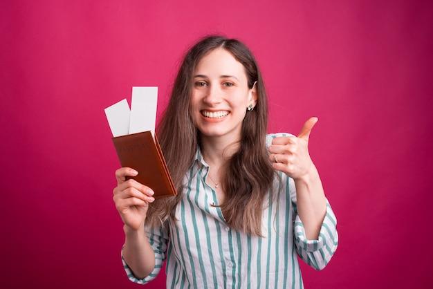 De gelukkige glimlachende jonge vrouw toont duim terwijl het houden van haar paspoort met kaartjes