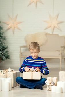 De gelukkige glimlachende jongen houdt de doos van de kerstmisgift tegen de achtergrond van het decor van het nieuwjaar.