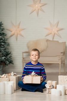 De gelukkige glimlachende jongen houdt de doos van de kerstmisgift tegen het decor van het nieuwjaar.