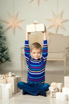 De gelukkige glimlachende jongen houdt de doos van de kerstmisgift