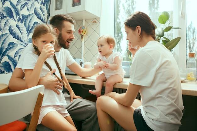 De gelukkige glimlachende kaukasische familie in de keuken die ontbijt voorbereidt
