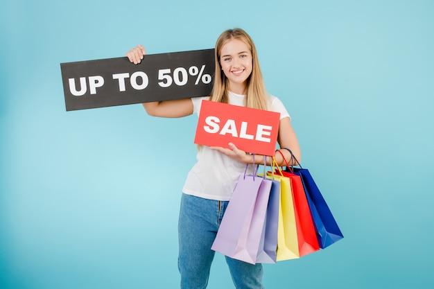 De gelukkige glimlachende mooie vrouw met verkoop tot 50% ondertekent en kleurrijke die het winkelen zakken over blauw wordt geïsoleerd
