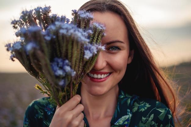 De gelukkige glimlachende vrouw behandelt de vloer van haar gezicht met een boeket van purpere bloemenclose-up