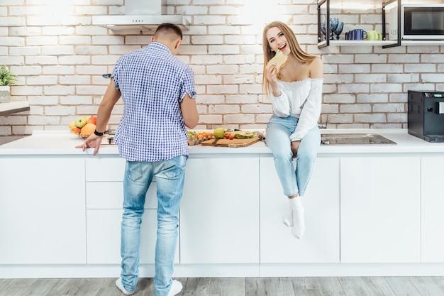 De gelukkige glimlachende vrouw eet sandwich terwijl haar echtgenoot het voorbereidingen treffen eet