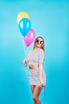 De gelukkige glimlachende vrouw kijkt op lucht kleurrijke ballons die pret over een blauwe achtergrond hebben.