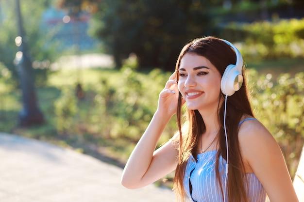De gelukkige glimlachende vrouw luistert in openlucht aan muziek in haar hoofdtelefoons in het park.