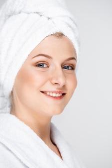 De gelukkige glimlachende vrouw past gezichtscrème, huidverzorgingconcept toe
