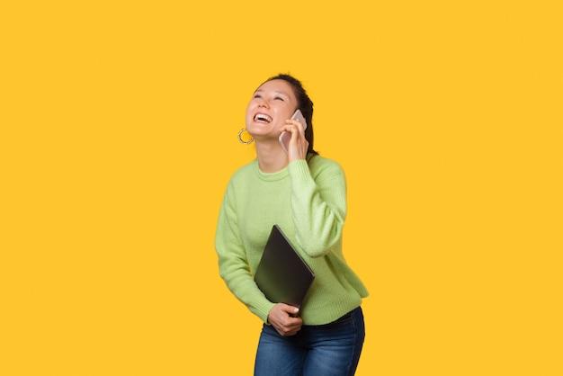 De gelukkige glimlachende vrouw spreekt op de telefoon terwijl het houden van haar laptop