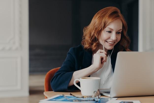 De gelukkige glimlachende vrouwelijke ondernemer heeft online conferentie via moderne laptop computer