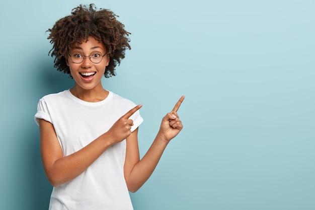 De gelukkige glimlachende vrouwenverkoper wijst naar de rechterbovenhoek, adverteert item op lege ruimte, heeft vriendelijke gezichtsuitdrukking
