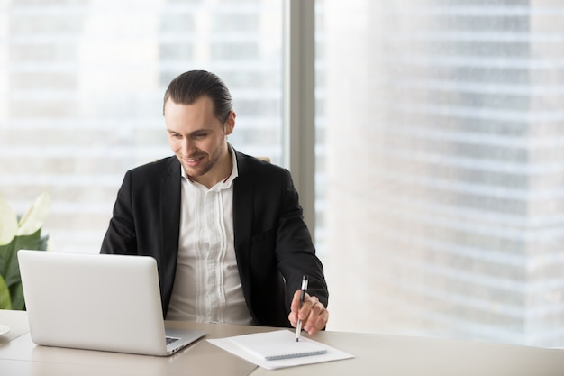 De gelukkige glimlachende zakenman die in bureau laptop bekijken sreen.