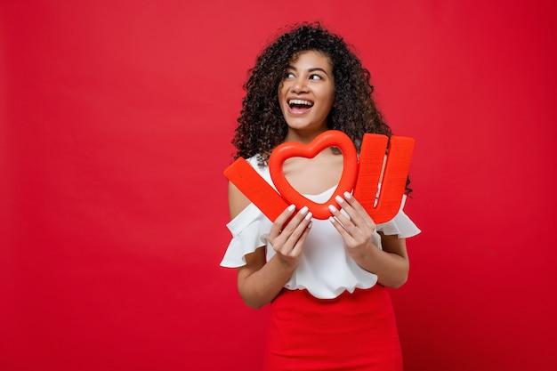 De gelukkige glimlachende zwarte meisjesholding i houdt van u brieven met hartvorm die op rood wordt geïsoleerd