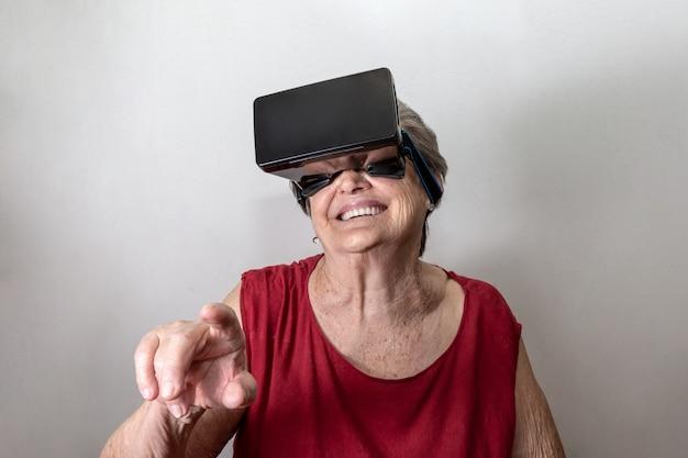 De gelukkige grootmoeder gebruikt modern vr-beschermende brilglas op witte achtergrond. nieuwe trends en technologieconcept en grappige actieve ouderen.