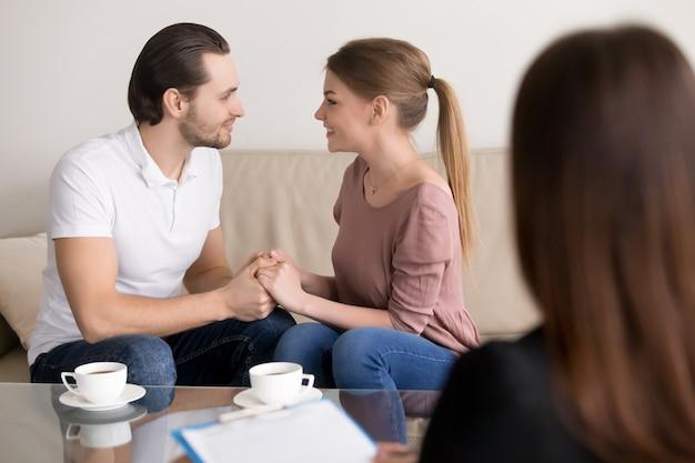 De gelukkige het glimlachen jonge handen van de paarholding, raadplegende psycholoog, die huwelijk plannen