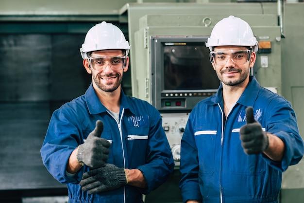 De gelukkige het glimlachen van het arbeidersteam hand toont duim voor het goede werken in fabriek.