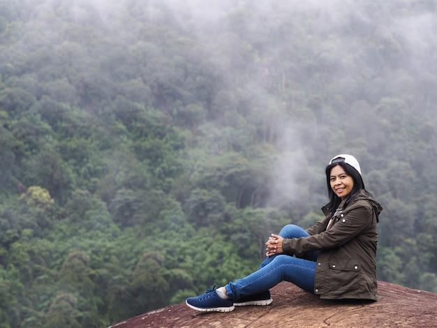 De gelukkige het glimlachen zitting van de vrouwentoerist over groen regenwoud