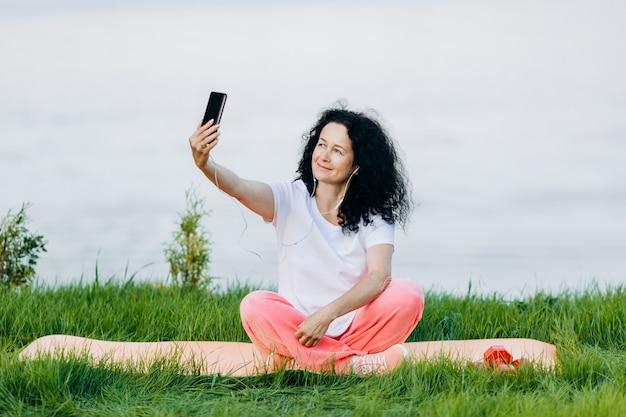 De gelukkige hogere vrouwenzitting op yogamat openlucht in oortelefoon en neemt een selfiebeeld.