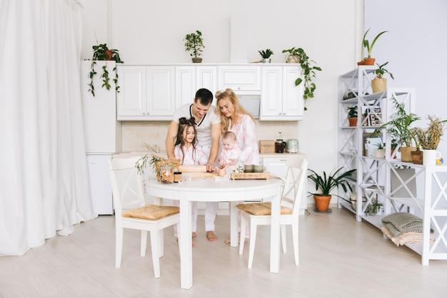 De gelukkige houdende van familie bereidt samen bakkerij voor. de moedervader en het twee dochtermeisje koken koekjes en hebben pret in de keuken. zelfgemaakt eten en kleine helper.