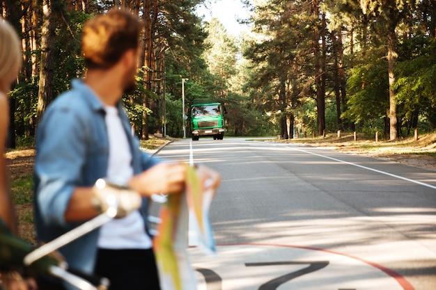 De gelukkige houdende van kaart van de paarholding in openlucht dichtbij autoped Gratis Foto