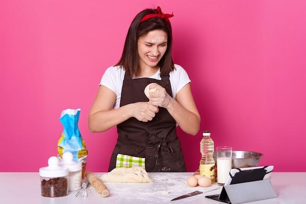 De gelukkige huisvrouw draagt keukenschort vuil met bloem, rode hoofdband, kneedt deeg terwijl het hebben van videocall met haar echtgenoot