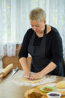 De gelukkige huisvrouw in een schort beeldhouwt rauw pizzadeeg met haar handen.