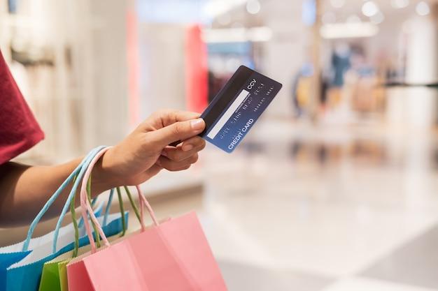 De gelukkige jonge aziatische creditcard van de vrouwenholding en kleurrijke het winkelen zakken, het concept van de vrouwenlevensstijl Premium Foto