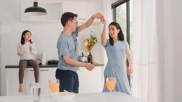 De gelukkige jonge aziatische familie luistert thuis aan muziek en dansend na ontbijt. aantrekkelijke japanse moeder vader en kind dochter genieten van tijd samen doorbrengen in de moderne keuken in de ochtend.