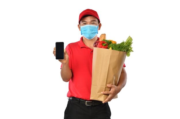 De gelukkige jonge aziatische leveringsmens in rood uniform, medisch gezichtsmasker, beschermende handschoenen draagt kruidenierswinkelzak die mobiele telefoon toont die op witte achtergrond wordt geïsoleerd