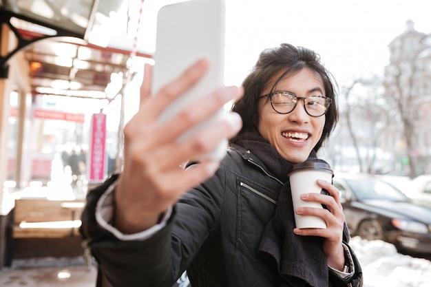 De gelukkige jonge aziatische mens het drinken koffie en maakt selfie.