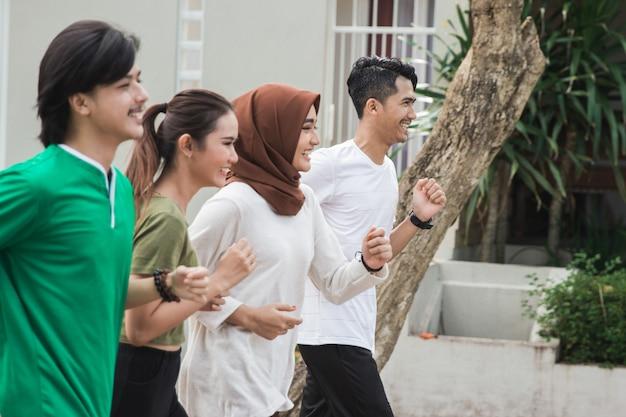 De gelukkige jonge aziatische mensen oefenen uit en warmen op