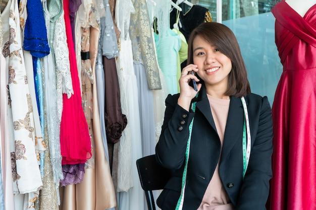 De gelukkige jonge aziatische modeontwerper van de vrouwennaaister gebruikt een smartphone om bestellingen van de klant te accepteren.