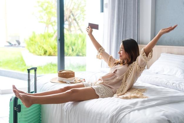 De gelukkige jonge aziatische reizigersvrouw ontspant op bed in hotelruimte. reis-, zomer-, weekendconcept.
