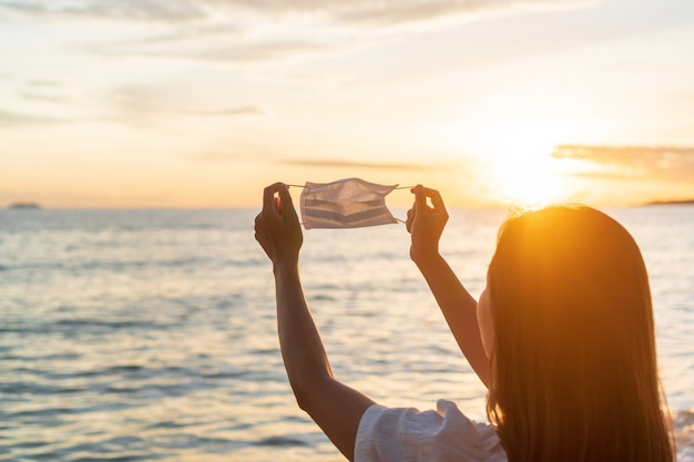 De gelukkige jonge aziatische reizigersvrouw stijgt beschermend gezichtsmasker op en houdt haar hand op het strand.