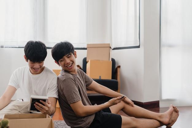 De gelukkige jonge aziatische vrolijke verhuizingen van de paarverhuizing vestigen zich in nieuw huis. asia lover guy lgbtq + open kartonnen doos of pakket uitpakken in woonkamer op verhuisdag. onroerend goed woning, lening en hypotheek.