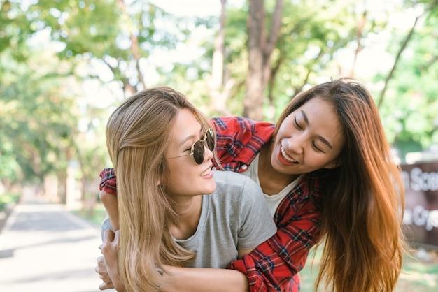 De gelukkige jonge aziatische vrouwen koppelen het spelen aan elkaar terwijl zij stadsreis doen