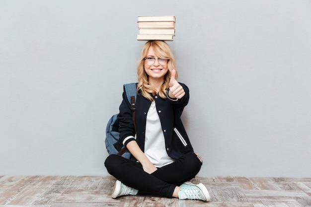 De gelukkige jonge boeken van de studenteholding op hoofd.