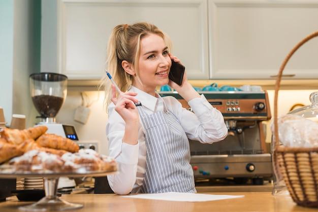 De gelukkige jonge eigenaar die van de bakkerijwinkel telefoonorde neemt
