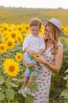 De gelukkige jonge familie, de moedervader en de zoon, glimlachen, houden en koesteren op het zonnebloemgebied