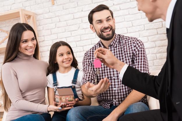 De gelukkige jonge familie krijgt sleutels tot nieuw huis van makelaar in onroerend goed.