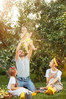 De gelukkige jonge familie tijdens het plukken appels in een tuin buitenshuis
