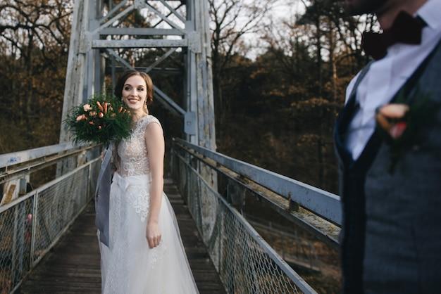 De gelukkige jonge glimlachende bruid en de bruidegom bevinden zich op de hangbrug. trouwfoto's op een interessante plek