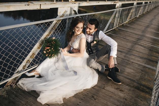 De gelukkige jonge glimlachende bruid en de bruidegom zitten op de hangbrug. zonnige trouwfoto's op een interessante plek